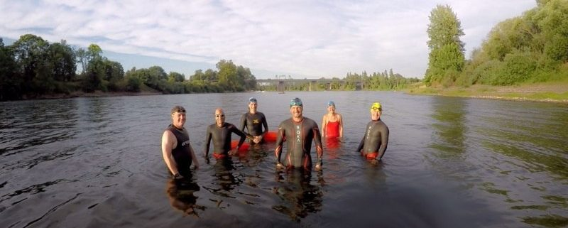 People posing for a photo while standing in the Willamette River in Salem in body suits. Willamette River Swim Clinics Available   Rotary Riverfest