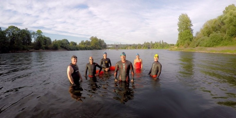 People posing for a photo while standing in the Willamette River in Salem in body suits. Willamette River Swim Clinics Available | Rotary Riverfest